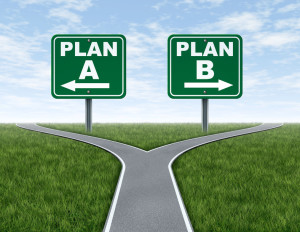 Cross roads with plan A plan B road signs business symbol represnting the difficult choices and challenges when selecting the right strategic path to take on a corporate decision.